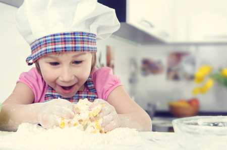 little dough: Cute little girl in apron baking cookies at home kitchen