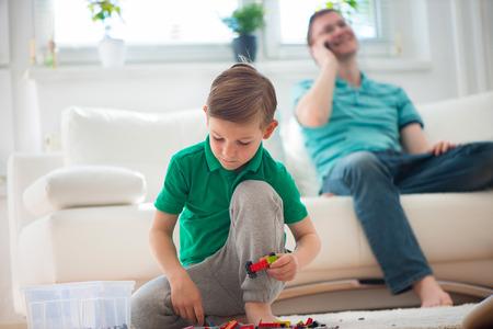 dos personas hablando: Juego del niño pequeño con los bloques, hablar con el padre telefon