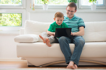 Happy father and child playing with laptop at home Stock Photo