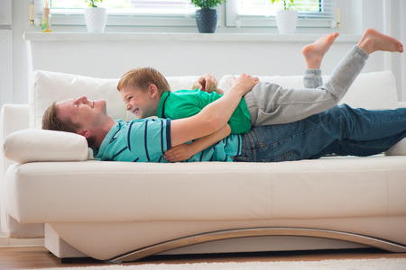 family tickle: Little boy having fun with father on sofa at home Stock Photo
