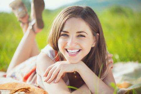 spring: Retrato de una mujer sonriente joven hermosa en la hierba Foto de archivo