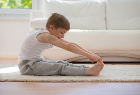 gymnastik: Glücklicher kleiner Junge, der Ausübung Sport zu Hause Lizenzfreie Bilder