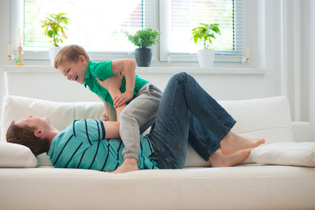 green couch: Little boy having fun with father on sofa at home Stock Photo