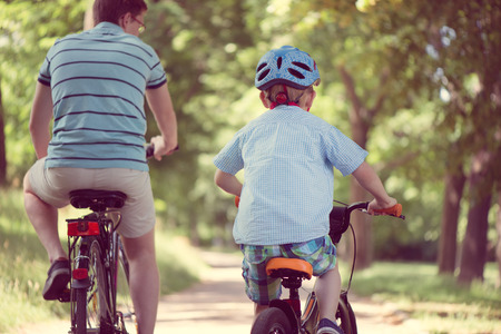 riding helmet: Happy father and son ride on bikes in summer park Stock Photo