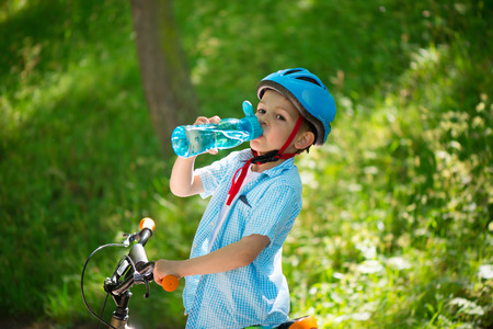 Little boy with bicycle drinks water summer in park