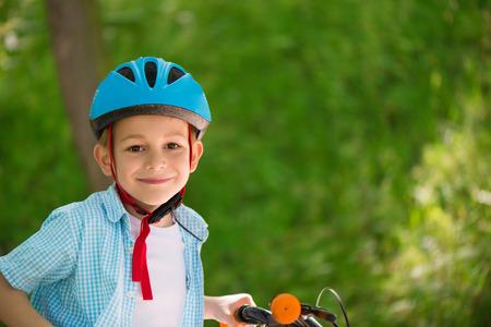 Schattige kleine jongen in helm op de fiets in het bos Stockfoto