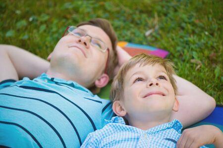 soñando: Padre joven con poco sol soñando en el parque de verano