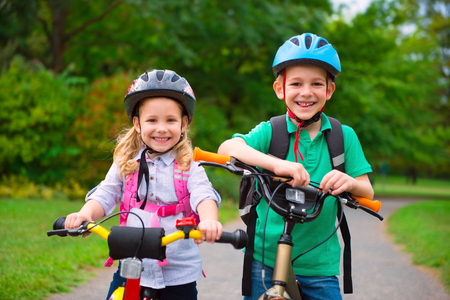 Two cute children cycling in summer park