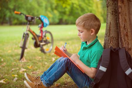 Portret van een leuke jongen, tekent hij in het park Stockfoto