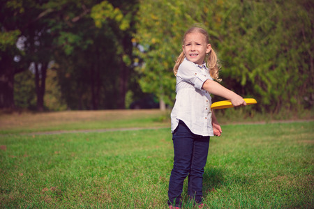 little one: One little girl play frisby in park Stock Photo