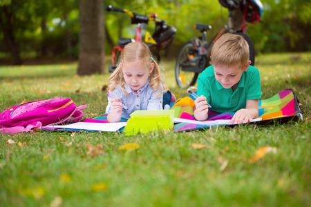 niños estudiando: Dos niños felices de dibujo en el parque sommer