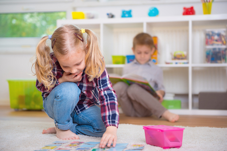 woman sitting on floor: Cute little girl play board game, boy read book