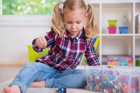 niñas jugando: Pretty chica inteligente jugar con bloques de juguete en casa