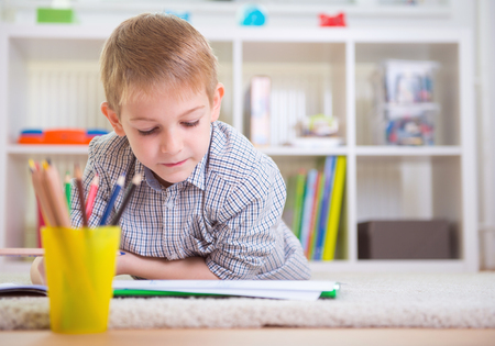 One adorable boy draws on floor at home Stock Photo