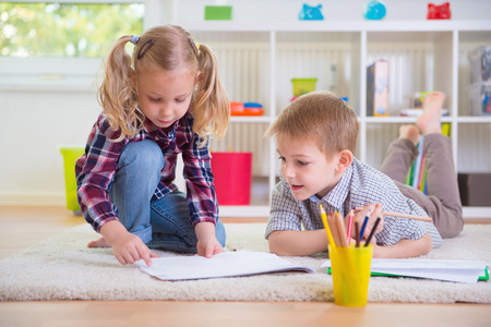 Two cute children draws on floor at home Stock Photo