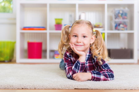 interrior: Cute little girl lay on carpet at home Stock Photo