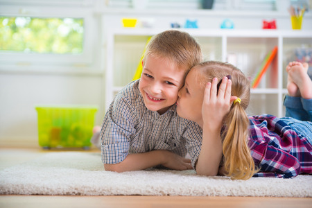brothers: Little girl kiss her happy brother at home