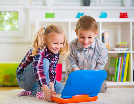 juguetes: Niños felices que juegan con la computadora portátil de juguete en casa Foto de archivo