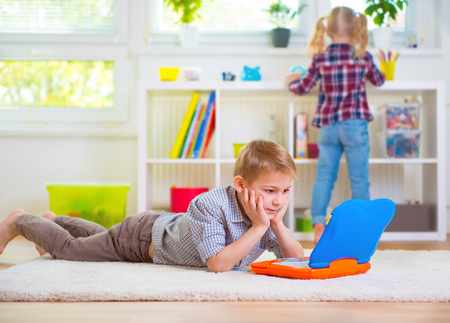 Little intelligent boy play with toy laptop at home Standard-Bild