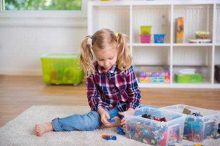 one room school house: Pretty clever girl play with toy blocks at home