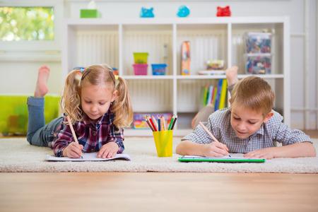 tarea escolar: Dos niños lindos dibuja en el piso en el hogar Foto de archivo