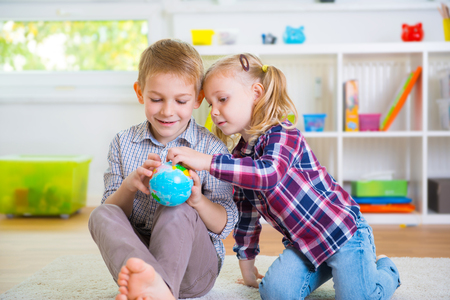 family playing: Two happy clever children exploring ball globe
