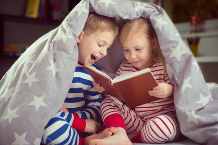 joy of reading: Two happy siblings reading book under the cover Stock Photo