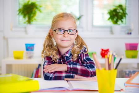 diligente: Muchacha bastante diligente en vasos aprende en la escuela Foto de archivo