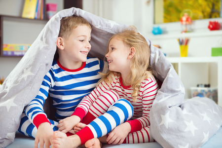 sibling: Two happy sibling children hiding under blanket Stock Photo