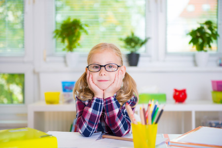 learns: Pretty diligent girl in glasses learns at school Stock Photo