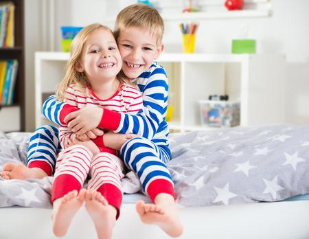 Twee gelukkige broers en zussen in de gestreepte sleepwears in bed