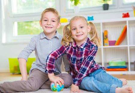 niños felices: Feliz de dos niños inteligentes que exploran Globo de la bola Foto de archivo