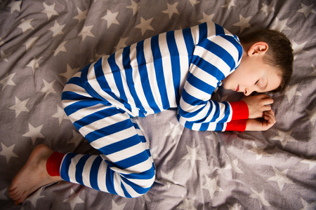 striped pajamas: Cute little boy sleeps in striped pajames on bed. Fokus above Stock Photo