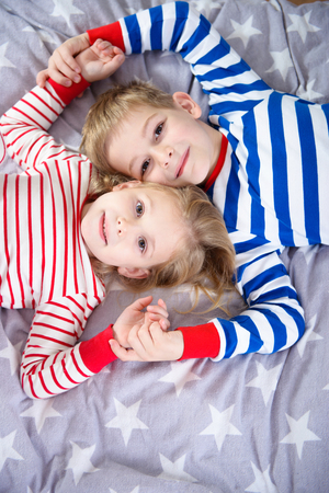 girl looking up: Two cute siblings lying in sleepwear on bed. Fokus frome above