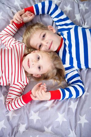 sleepwear: Two cute siblings lying in sleepwear on bed. Fokus frome above