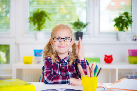 caucasian children: Pretty diligent girl in glasses learns at school Stock Photo