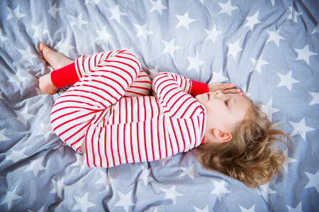 striped pajamas: Cute little girl sleeps in striped pajames on bed