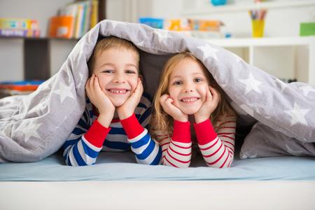 Two happy sibling children lying under blanket Foto de archivo