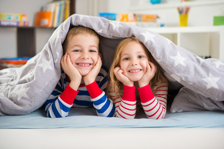 sheets: Two happy sibling children lying under blanket Stock Photo
