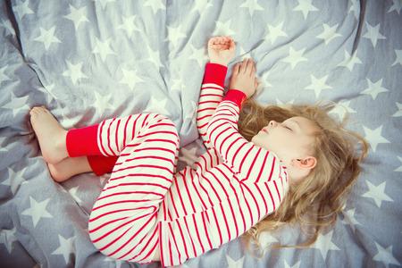 enfant qui dort: Cute petite fille dort dans pajames rayures sur lit Banque d'images