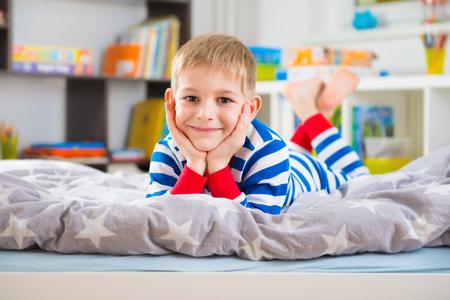 pijama: Niño pequeño lindo con un pijama de rayas encuentra en la cama