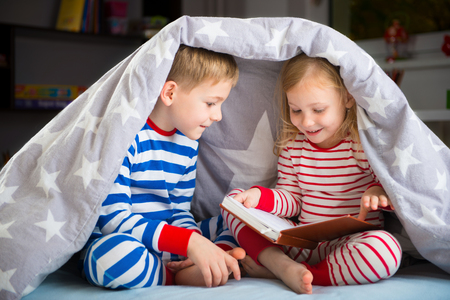 blanket: Two happy siblings reading book under the cover Stock Photo
