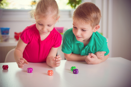 Two happy children playing with dices at home Фото со стока - 47783995