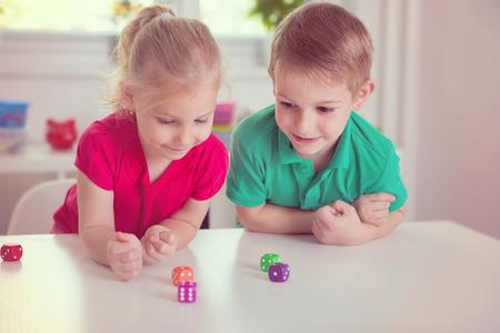 jugando: Dos niños felices jugando con dados en el hogar