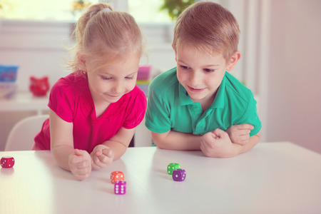 little table: Two happy children playing with dices at home