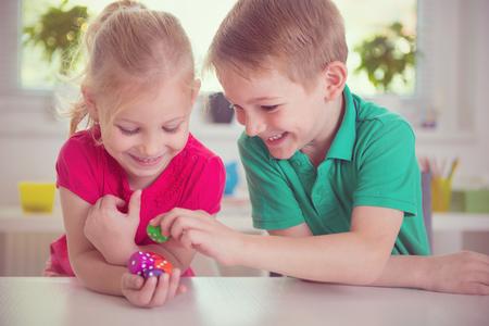 niño y niña: Dos niños felices jugando con dados en el hogar