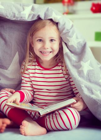 striped pajamas: Pretty little girl in sleepwear sitting with book under blanket Stock Photo