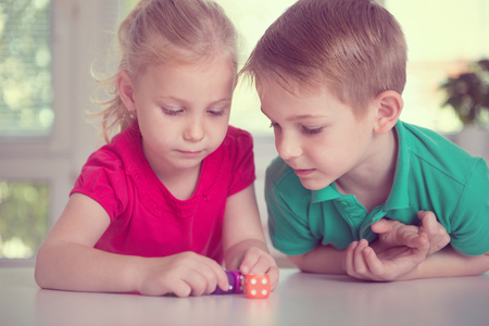 two children: Two happy children playing with dices at home