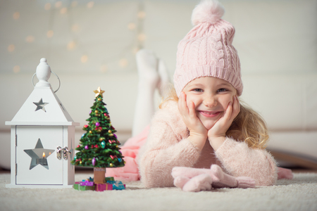 pink christmas: Portrait of ptetty little girl with new years tree and flashlight at christmas time