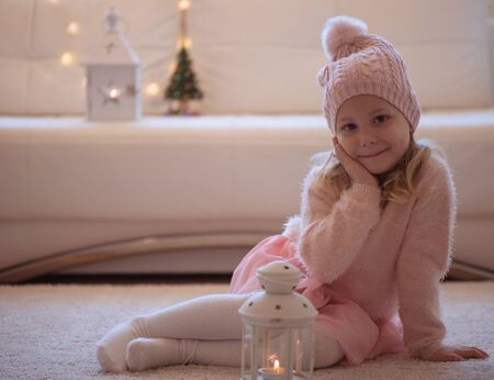 pink christmas: Portrait of cute little girl in hat and gloves at Christmas time